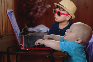 a baby and a child with glasses pretending to build a website on a laptop.
